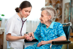 Caregiver is checking the vital signs of the old lady